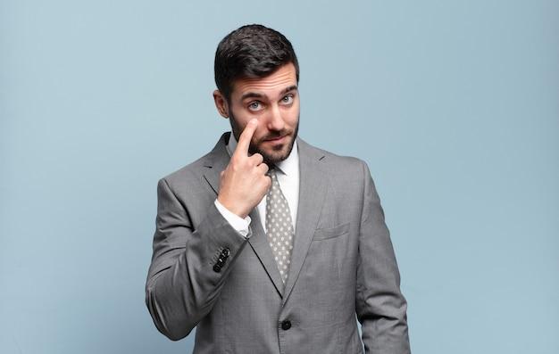 Jeune adulte bel homme d'affaires gardant un œil sur vous, ne faisant pas confiance, regardant et restant alerte et vigilant