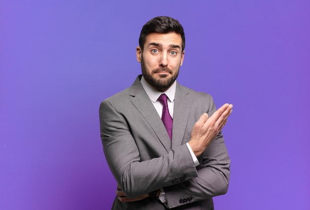 Jeune adulte bel homme d'affaires se sentant confus et désemparé, s'interrogeant sur une explication ou une pensée douteuse