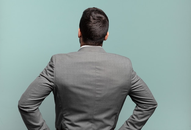 Jeune adulte bel homme d'affaires se sentant confus ou plein ou des doutes et des questions, se demandant, avec les mains sur les hanches, vue arrière