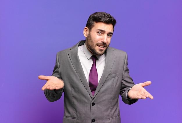 Jeune adulte bel homme d'affaires se sentant désemparé et confus, ne sais pas quel choix ou option choisir, se demandant