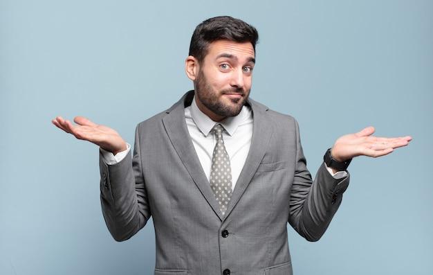 Jeune adulte bel homme d'affaires se sentant perplexe et confus, doutant, pondérant ou choisissant différentes options avec une expression amusante