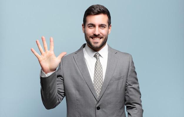 Jeune adulte bel homme d'affaires souriant et à la recherche amicale, montrant le numéro cinq ou cinquième avec la main en avant, compte à rebours