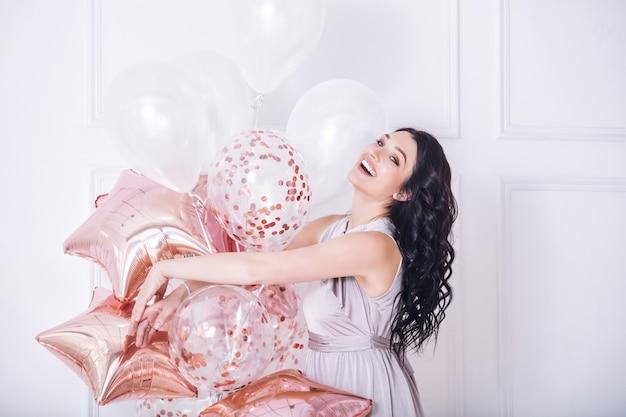 Jeune adulte belle femme en longue robe de vacances à la mode avec des ballons roses