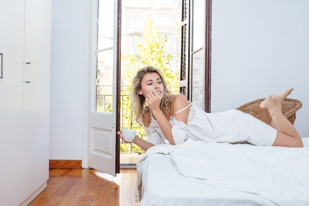 Jeune adulte belle femme matin à la maison dans la chambre en robe blanche avec une tasse de café