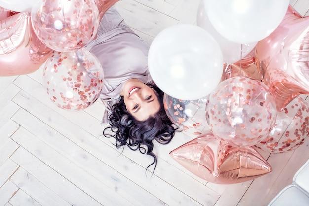 Jeune adulte belle femme en robe de vacances à la mode avec des ballons roses allongé sur le plancher en bois