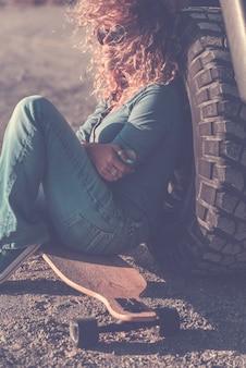 Jeune adulte belle femme s'asseoir sur la route sur un long skateboard et une roue de voiture à l'arrière - concept de voyage et de style de vie actif et élégant en plein air - vie de voyage d'aventure féminine