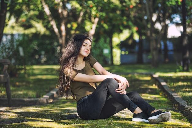 Jeune adulte belle fille brune en vêtements décontractés heureux assis sur moussu dans le parc