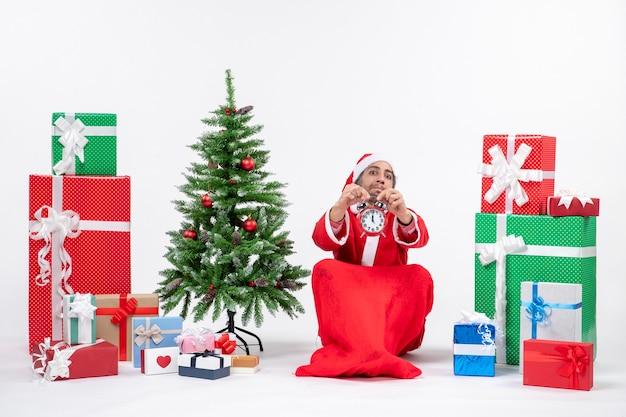 Jeune adulte célébrer les vacances de noël assis dans le sol et montrant l'horloge près de cadeaux et arbre de noël décoré