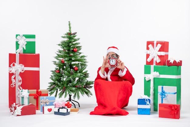 Jeune adulte célébrer les vacances de noël assis dans le sol et tenant une horloge près de cadeaux et arbre de noël décoré