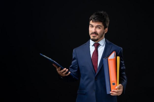 Jeune adulte confiant en costume tenant plusieurs documents sur un mur sombre isolé