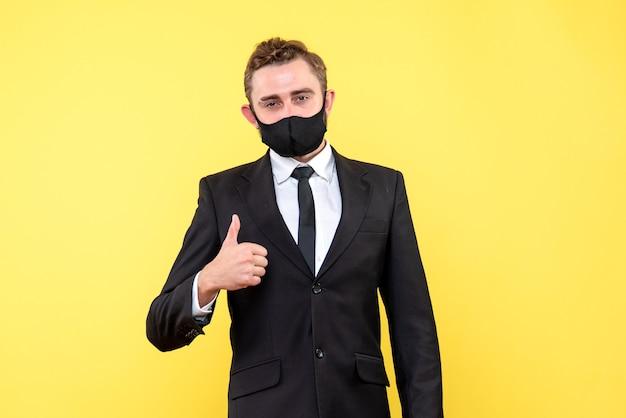 Jeune adulte avec costume et cravate montrant signe ok avec son pouce sur jaune