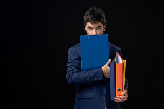 Jeune adulte en costume tenant plusieurs documents et posant sur un mur sombre isolé