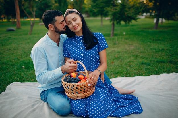 Jeune adulte femme et homme couple pique-nique assis avec panier de fruits au pré d'herbe verte dans le parc.
