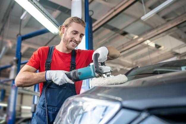 Jeune adulte homme confiant en uniforme de travail travaillant sur des voitures