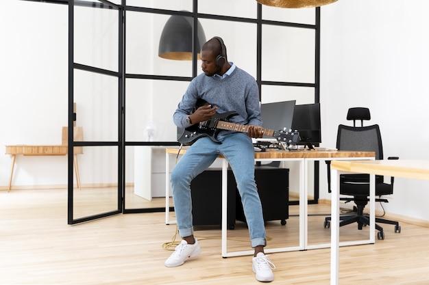 Jeune adulte jouant de la guitare