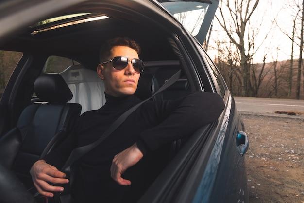 Jeune adulte de race blanche à l'intérieur d'une voiture de sport