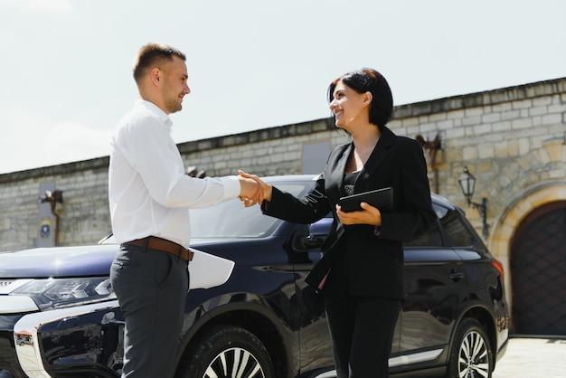 Jeune adulte souriant homme et femme en affaires costumes sombres debout près d'une voiture serrant la main
