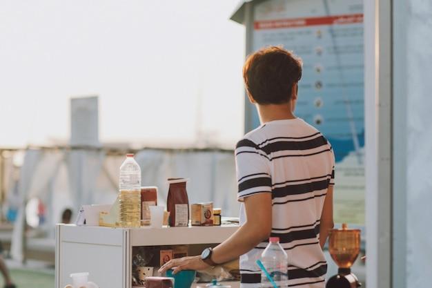Jeune adulte vendant des produits sur le marché en plein air