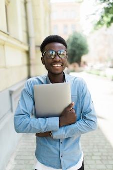 Jeune, africaine, debout, célébrer, succès, rue, regarder, sien, ordinateur portable, main