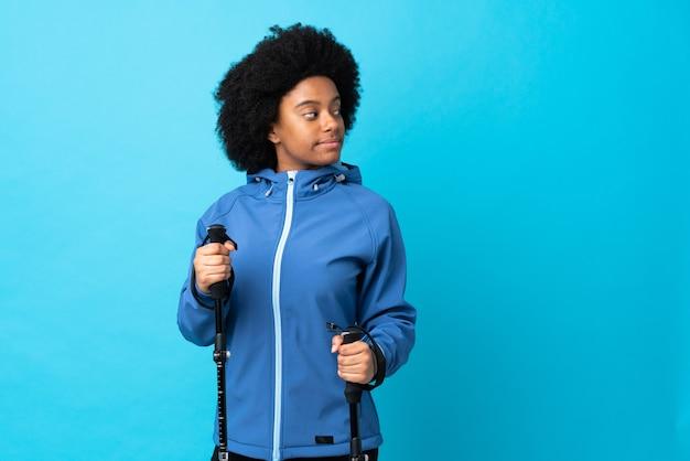 Jeune afrique américain avec sac à dos et bâtons de randonnée isolés sur bleu. portrait