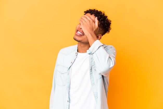Jeune afro-américain bouclé isolé sur violet rit joyeusement en gardant les mains sur la tête. notion de bonheur.
