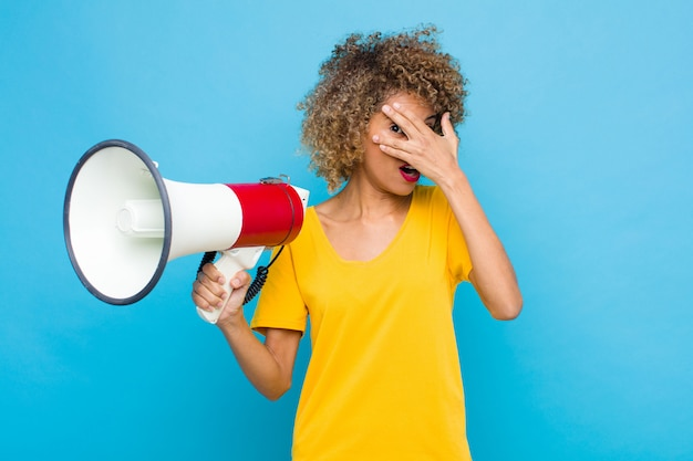 Jeune afro-américain choqué, effrayé ou terrifié, couvrant le visage avec la main et furtivement entre les doigts avec un mégaphone