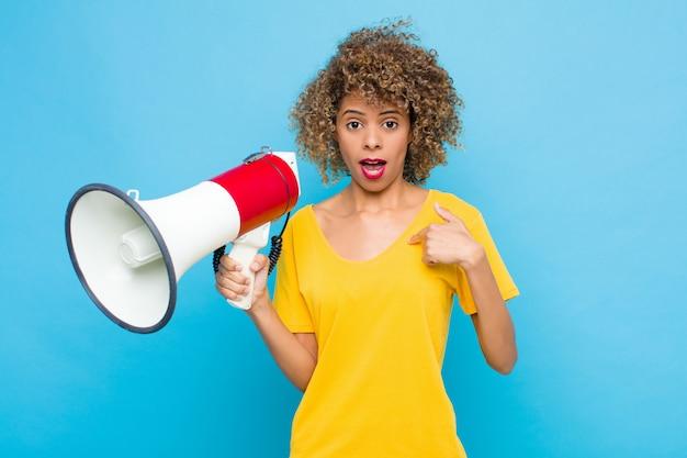 Jeune afro-américain à choqué et surpris avec la bouche grande ouverte, pointant vers soi avec un mégaphone