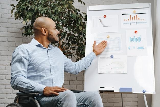 Un jeune afro-américain handicapé en fauteuil roulant fait une présentation au bureau sur un tableau blanc