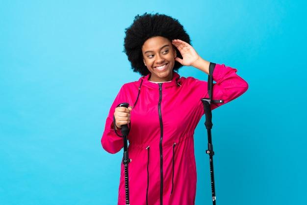 Jeune afro-américain avec sac à dos et bâtons de randonnée isolé sur fond bleu en écoutant quelque chose en mettant la main sur l'oreille
