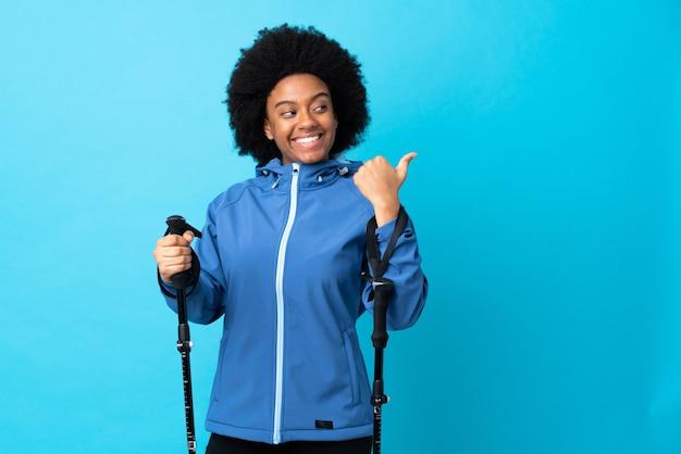 Jeune afro-américain avec sac à dos et bâtons de randonnée isolé sur fond bleu pointant vers le côté pour présenter un produit