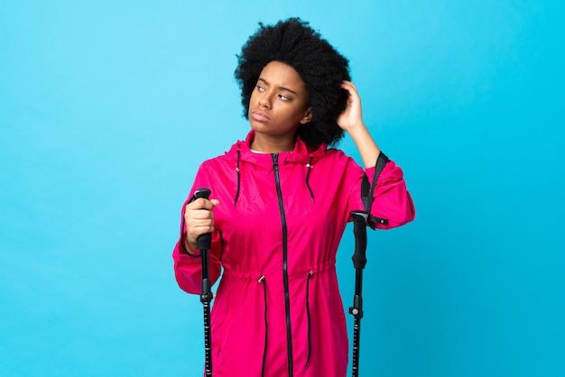 Jeune afro-américain avec sac à dos et bâtons de randonnée isolé sur mur bleu ayant des doutes en se grattant la tête