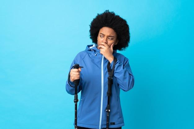 Jeune afro-américain avec sac à dos et bâtons de randonnée isolés sur bleu ayant des doutes et avec l'expression du visage confus