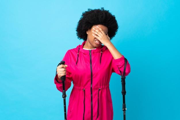 Jeune afro-américain avec sac à dos et bâtons de randonnée isolés sur bleu avec maux de tête