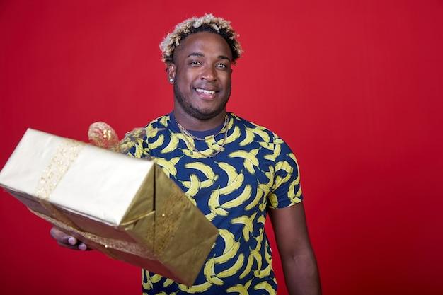 Le jeune afro-américain souriant donne un cadeau dans un paquet d'or sur fond rouge