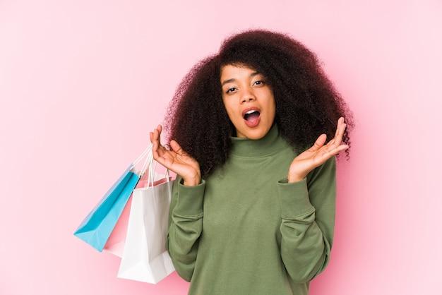 Jeune, afro, femme, achats, isolé jeune, afro, femme, achat, isolayoung, afro, femme, tenue, a, roses, isolé, surpris et choqué. <mixto>