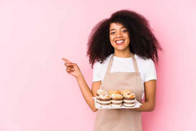 Jeune afro pâtissier femme tenant un cupcakes isolé jeune femme afro boulangère souriant et pointant de côté, montrant quelque chose à l'espace vide.