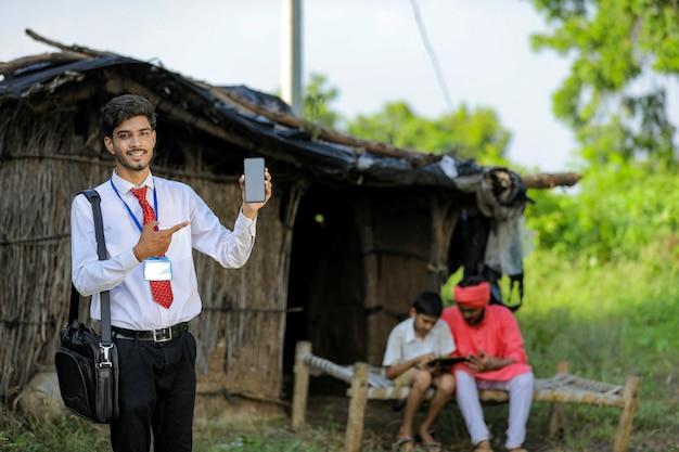 Jeune agent de banque indienne montrant écran mobile avec agriculteur