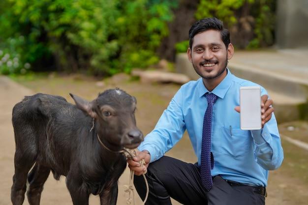 Jeune agent d'élevage indien ou banquier avec veau et montrant un smartphone.