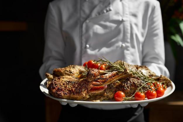 Jeune agneau fraîchement cuit servi par l'assiette du serveur. agneau au barbecue et lit de romarin