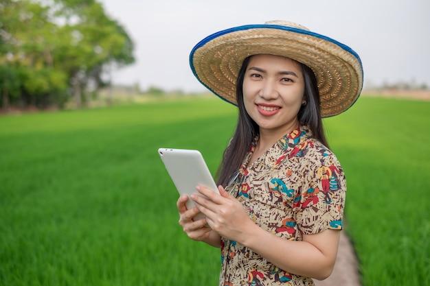 Jeune agriculteur asiatique femme sourire face stand et à l'aide de tablette mobile à la ferme de riz vert