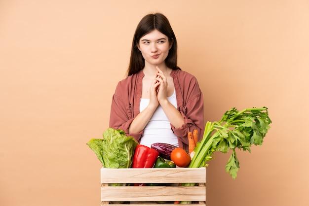 Jeune agriculteur femme avec des légumes fraîchement cueillis dans une boîte complotant quelque chose