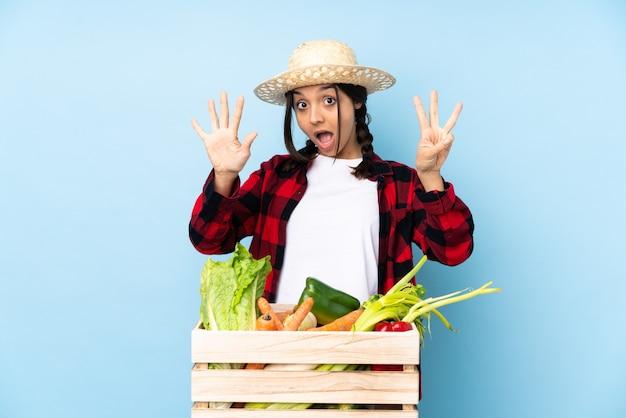 Jeune agriculteur femme tenant des légumes frais dans un panier en bois comptant huit avec les doigts