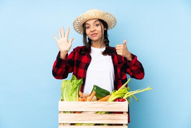 Jeune agriculteur femme tenant des légumes frais dans un panier en bois comptant six avec les doigts