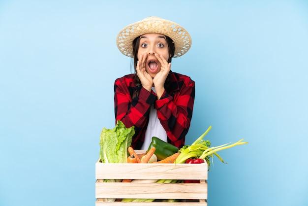 Jeune agriculteur femme tenant des légumes frais dans un panier en bois criant et annonçant quelque chose