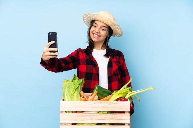 Jeune agriculteur femme tenant des légumes frais dans un panier en bois faisant un selfie