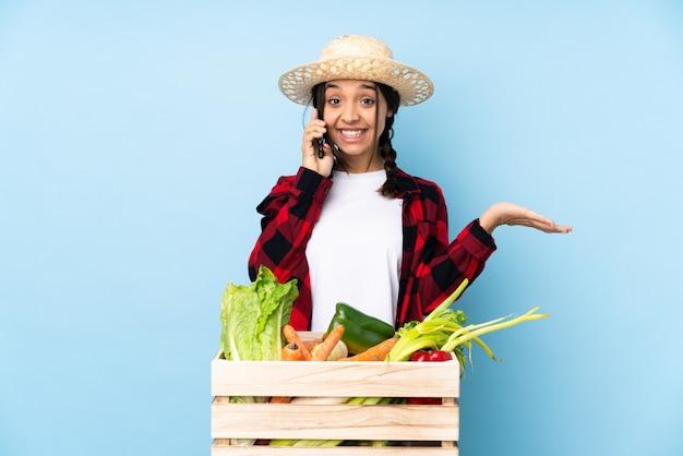 Jeune agriculteur femme tenant des légumes frais dans un panier en bois, gardant une conversation avec le téléphone mobile avec quelqu'un