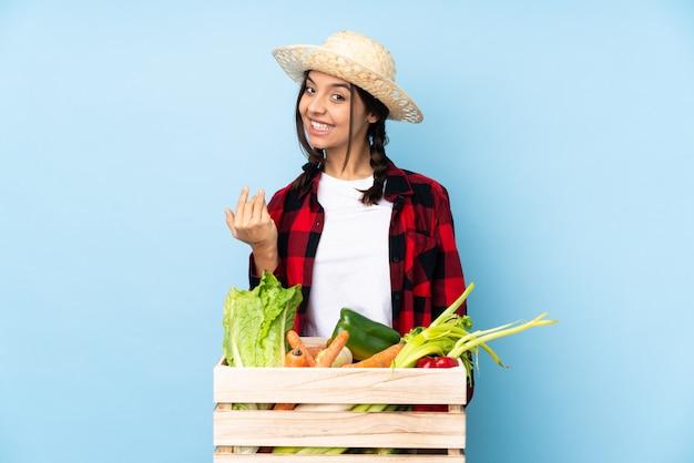 Jeune agriculteur femme tenant des légumes frais dans un panier en bois invitant à venir avec la main.