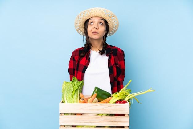 Jeune agriculteur femme tenant des légumes frais dans un panier en bois et levant