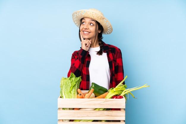 Jeune agriculteur femme tenant des légumes frais dans un panier en bois en pensant à une idée tout en levant