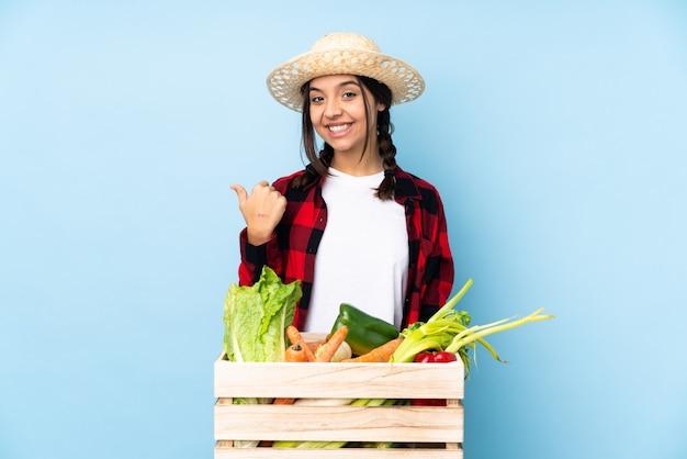 Jeune agriculteur femme tenant des légumes frais dans un panier en bois pointant vers le côté pour présenter un produit